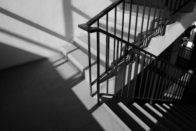 Modernes metallgeländer am treppenhaus mit schatten in einem modernen konkreten gebäude