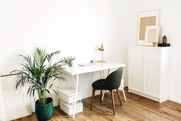 Modernes minimalistisches skandinavisches nordisches innendesignkonzept. home-office-arbeitsbereich mit tisch, stuhl, handfläche