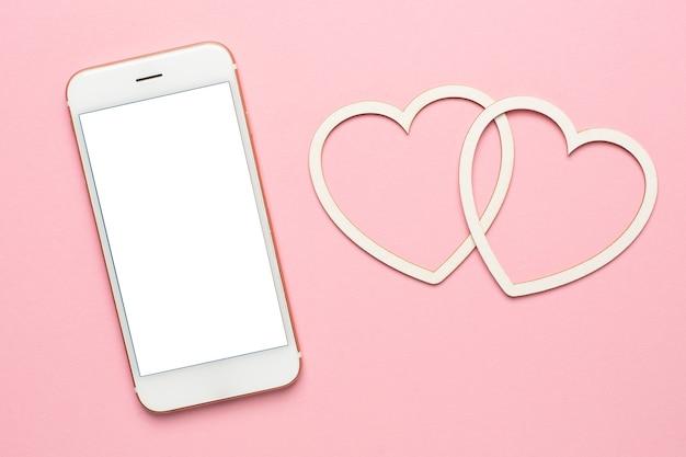 Modernes mobiltelefon mit herzen, sozialem distanzierungs- und datierungskonzept, valentinstagmodell, kopierraum auf der draufsicht