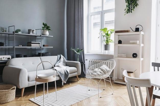Modernes nordisches wohnzimmer-interieur mit grauem design-sofa, couchtisch, pflanzen, stilvollen accessoires, dekoration, teppich und bücherständern in eleganter wohnkultur