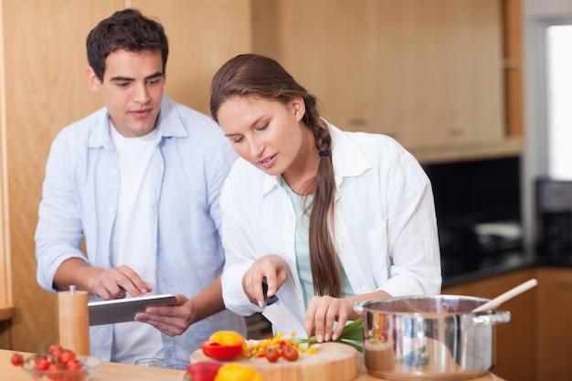 Modernes paar unter verwendung eines tablet-computers zum zu kochen
