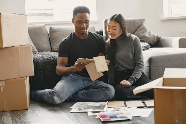 Modernes paar wählt farben für möbel. nettes paar, das in ihrem neuen zuhause auf dem boden sitzt.