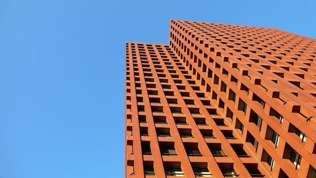 Modernes rotes farbobergeschossgebäude und strahlend blauer himmel