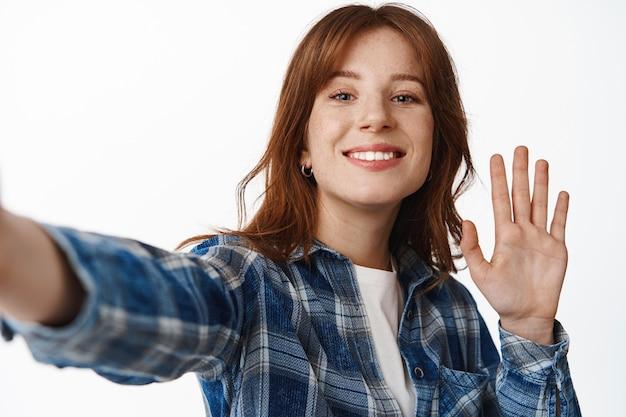 Modernes rothaarigemädchen-video-chat, handbewegung auf smartphone-kamera und lächeln, selfie machen, blog auf dem telefon aufzeichnen, das auf weiß steht.