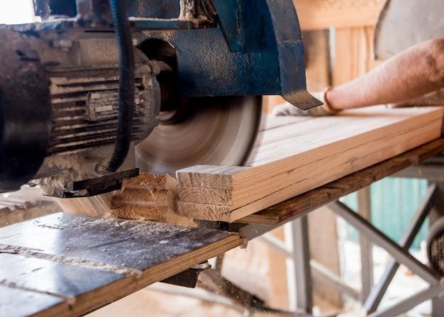 Modernes sägewerk. ein schreiner arbeitet an der holzbearbeitung der werkzeugmaschine.