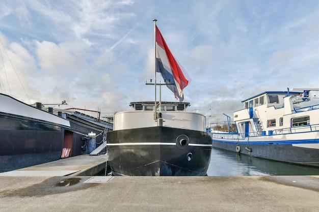 Modernes schiff mit flagge der niederlande nahe betonpfeiler gegen bewölkten blauen himmel im hafen