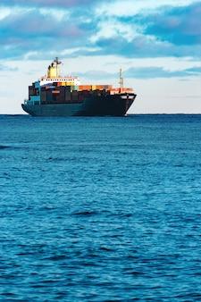 Modernes schwarzes containerschiff, das von der ostsee bewegt