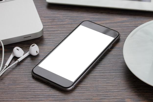 Modernes schwarzes smartphone, das auf arbeitstisch mit kopierraum auf bildschirm legt
