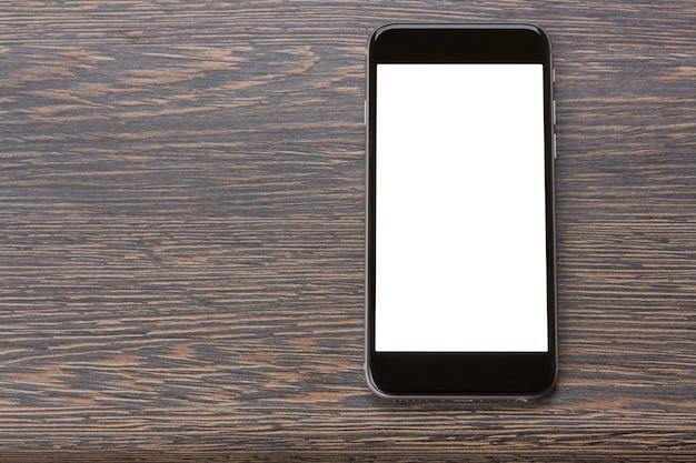 Modernes schwarzes smartphone, das auf holztisch mit kopienraum auf bildschirm legt