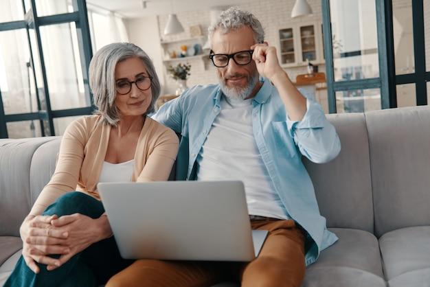 Modernes seniorenpaar in freizeitkleidung, das lächelt und laptop benutzt, während es zu hause zusammenhält?