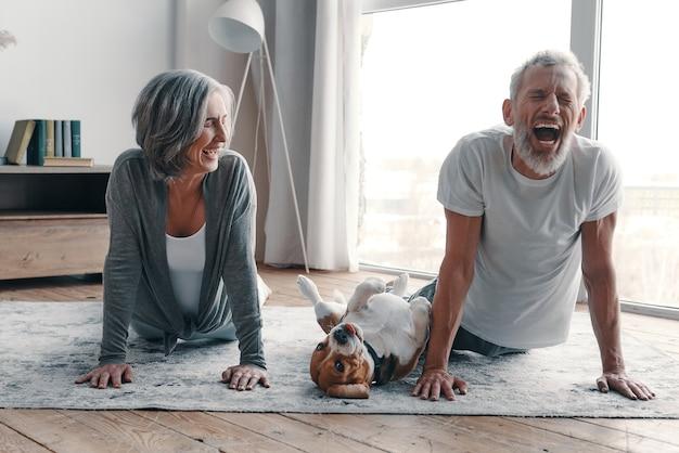 Modernes seniorenpaar in sportkleidung, das yoga macht und lächelt, während es zeit zu hause mit seinem hund verbringt