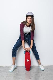 Modernes skatermädchen, das rotes skateboard auf dem boden lokalisiert auf weißer wand hält