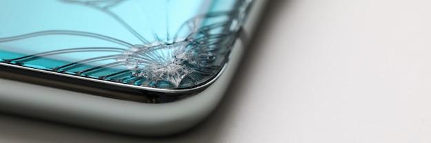 Modernes smartphone, das am tisch mit riss in der ecke liegt