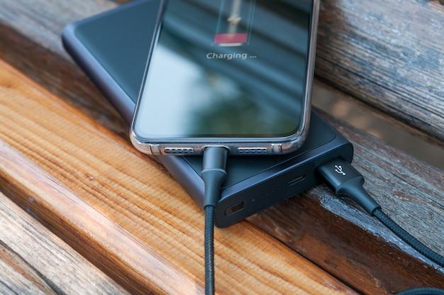 Modernes smartphone lädt von der powerbank