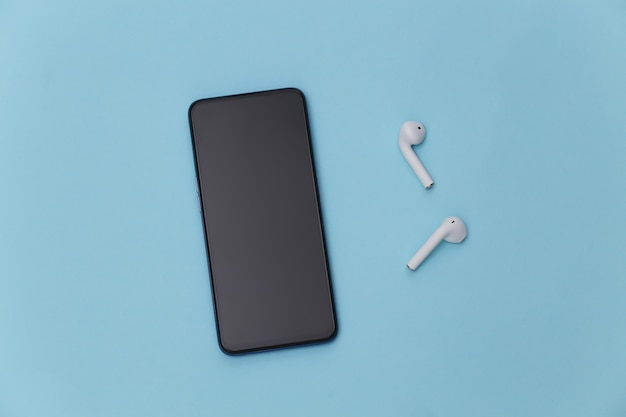 Modernes smartphone mit drahtlosen kopfhörern auf blauem pastellhintergrund.