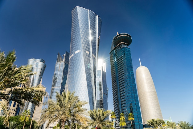 Modernes stadtzentrum mit türmen und wolkenkratzern am sonnigen himmel. doha, katar .