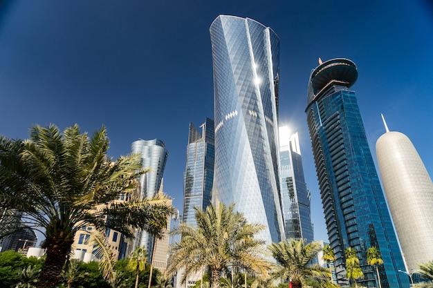 Modernes stadtzentrum mit türmen und wolkenkratzern am sonnigen himmel. doha, katar.