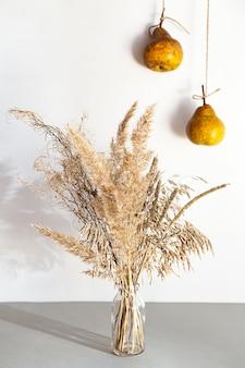 Modernes stillleben mit pampasgras in einer glasvase und birnen.