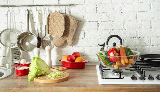 Modernes stilvolles kücheninterieur mit gemüse und früchten auf dem tisch.