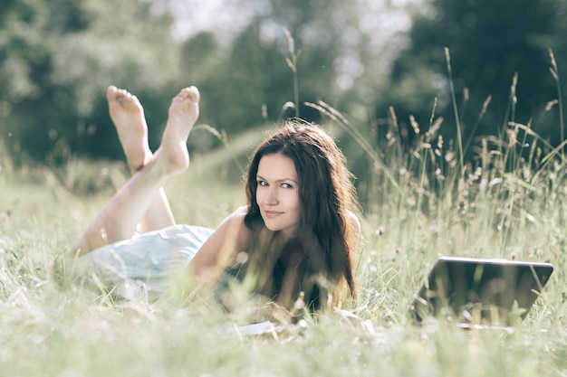 Modernes süßes mädchen relaxarea auf dem frischen gras. mensch und technik