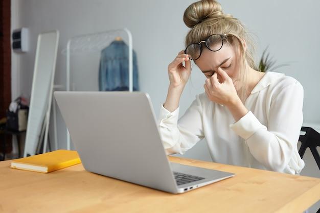 Modernes technologie-, job- und personenkonzept. porträt einer müden jungen mitarbeiterin mit haarknoten, die die brille abnimmt und ihren nasenrücken massiert und sich wegen viel arbeit gestresst fühlt