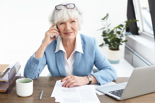 Modernes technologie-, kommunikations- und jobkonzept. hohe winkelansicht der erfolgreichen erfahrenen älteren geschäftsfrau, die anzug und stilvolles zubehör mit telefongespräch unter verwendung des handys trägt
