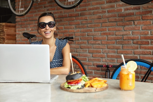 Modernes technologie- und kommunikationskonzept. hübsche freiberufliche frau in der sonnenbrille, die entfernt auf generischem laptop arbeitet, der am tisch mit frischem orangensaft und burger sitzt