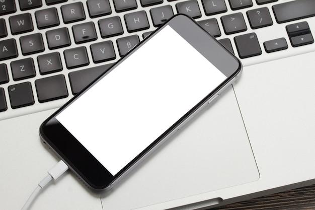 Modernes telefon, das auf laptop-tastatur mit kopierraum auf bildschirm legt