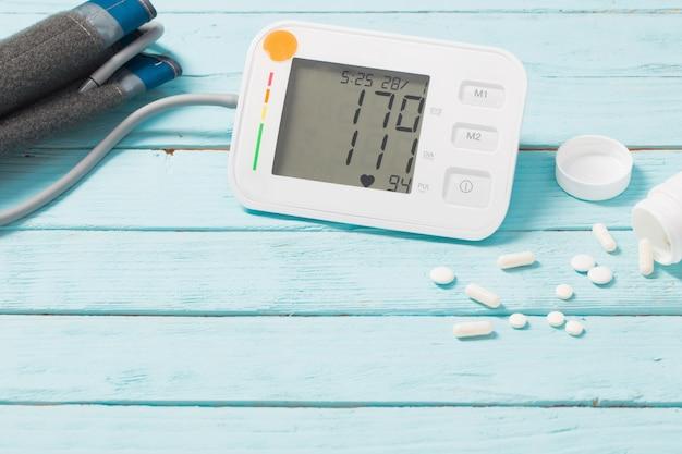 Modernes tonometer mit pillen auf hölzernem hintergrund