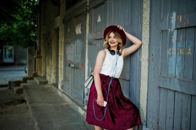 Modernes und schönes blondes vorbildliches mädchen im stilvollen roten samtvelourrock, in der weißen bluse und im hut, aufgeworfen mit telefon und kopfhörern.