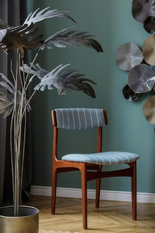 Modernes und stilvolles esszimmer mit eleganten stühlen, silberner pflanze und designdekoration. vorlage. wohnkultur. grüne hintergrundwand.