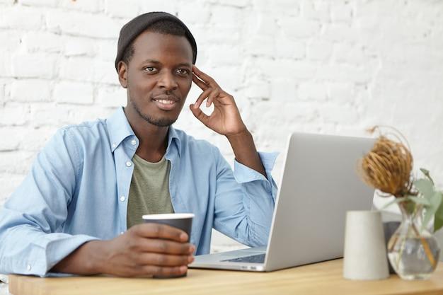 Modernes urbanes lifestyle- und technologiekonzept. attraktiver junger afroamerikanischer männlicher freiberufler, der hut trägt, der kaffeepause hat, während entfernt an laptop-pc arbeitet, nachdenklich oder verträumt aussieht