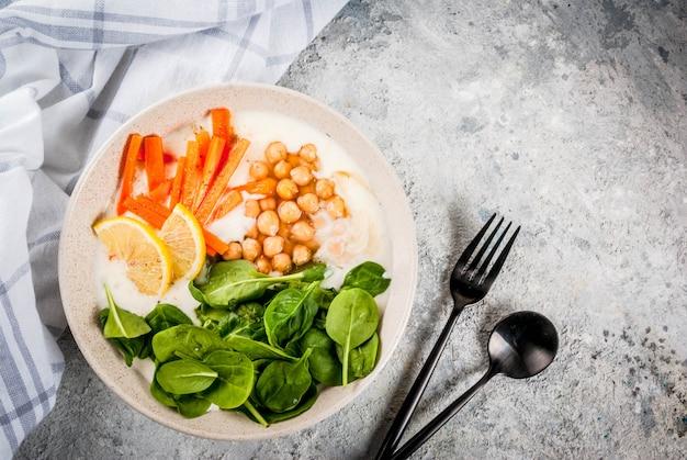 Modernes veganes essen, herzhafte joghurtschale mit bohnen, kichererbsen, spinat, würzigen karotten, zitrone