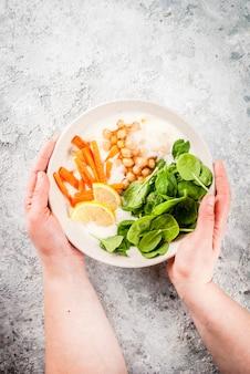 Modernes veganes essen, pikante joghurtschale mit bohnen, kichererbsen, spinat, würzigen karotten, zitronenjoghurtschale