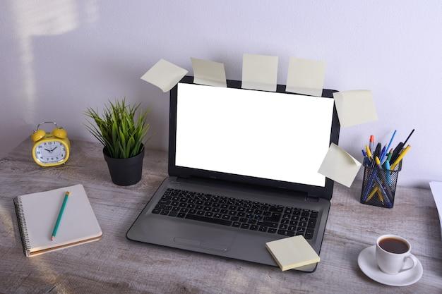Modernes weißes schreibtischtabellenmodell, arbeitsplatz mit laptop-computer mit weißem schirm für sie text oder bild, grünes gras, tasse kaffee und ein stapel papiere auf weißem felsenhintergrund.
