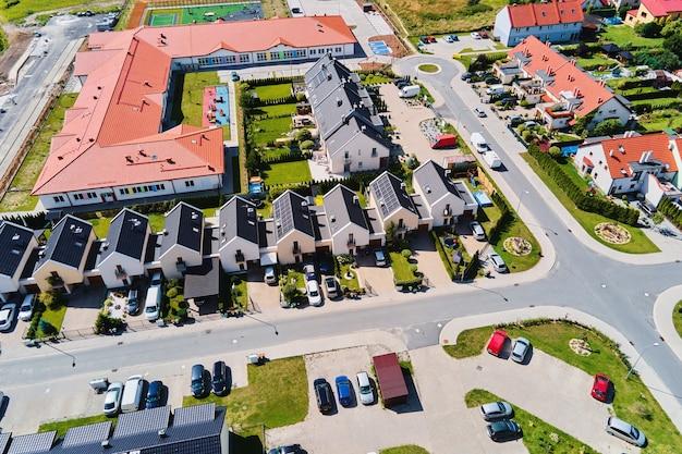Modernes wohnviertel in europa-stadt, luftbild. wohngegend im sonnenuntergang, vogelperspektive. stadtstraßen mit luxushausgebäuden und geparktem auto