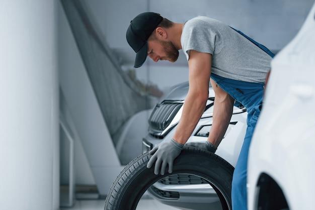 Modernes zimmer. mechaniker, der einen reifen an der reparaturwerkstatt hält wechsel von winter- und sommerreifen.
