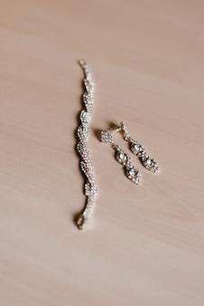 Modeschmuck: ohrringe und armband auf beiger hölzerner hintergrundnahaufnahme, selektiver fokus