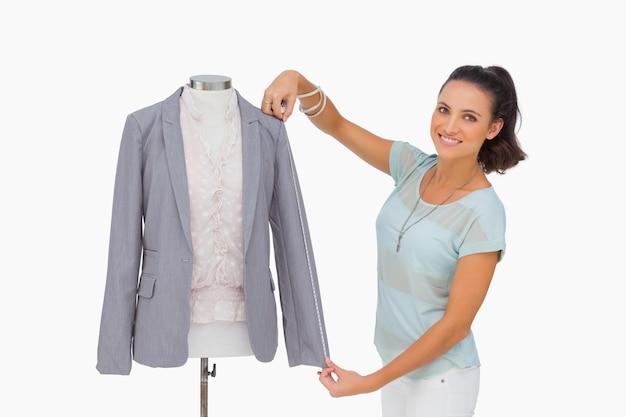 Modeschöpfer, der blazerärmel auf mannequin und dem lächeln misst