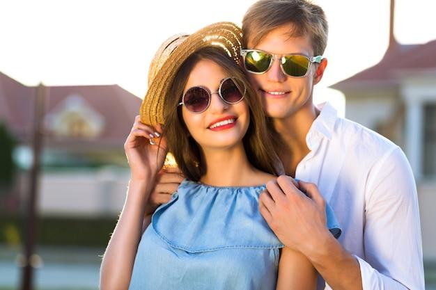 Modesommerbild des eleganten paares im vintage-stil am romantischen valentinstag, das eine tolle zeit zusammen hat, umarmungen und küsse, hipster, stilvolle kleidung und sonnenbrille, schöne liebhaber, familie im freien