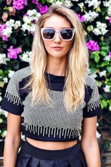 Modesommerporträt der trendigen stilvollen blonden frau, die gesamtrückblick und sonnenbrille trägt