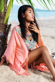 Modesommerporträt des jungen schönen asiatischen modells, das am tropischen strand entspannt, boho-trendkleid trägt, auf weißem sand nahe palme sitzend.