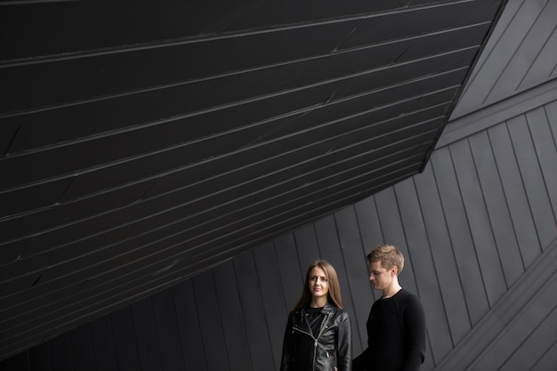 Modestilfoto des schönen paares auf schwarzer hintergrundwand
