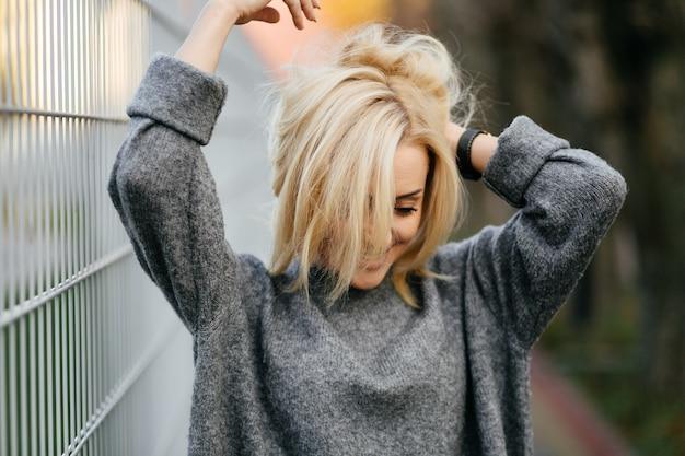 Modestraßenfotosession stilvoller junger dame in einer grauen kleidung