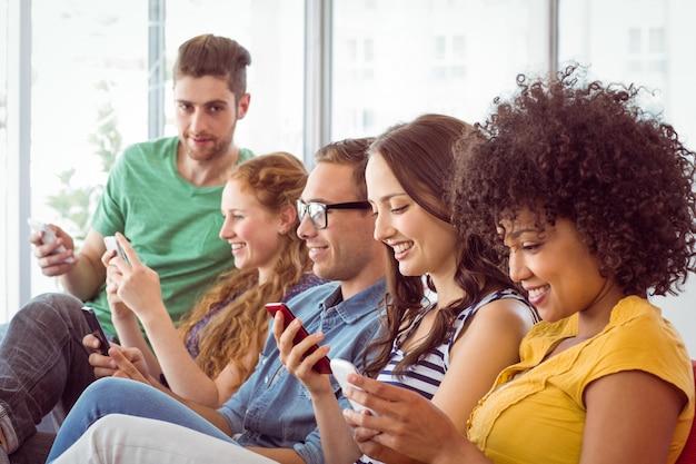 Modestudenten, die ihr smatphone betrachten
