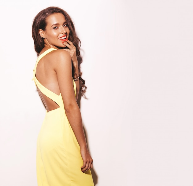 Modezauber stilvolles schönes modell der jungen frau mit den roten lippen im hellen gelben kleid des sommers lokalisiert auf weiß
