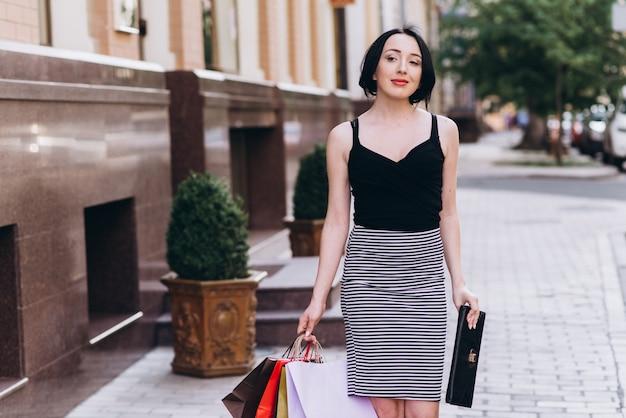 Modisch gekleidete frau, die auf den straßen mit farbigen einkaufstüten geht. einkaufskonzept
