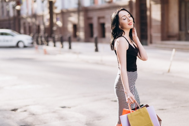 Modisch gekleidete frau mit farbigen einkaufstüten auf den straßen, einkaufskonzept