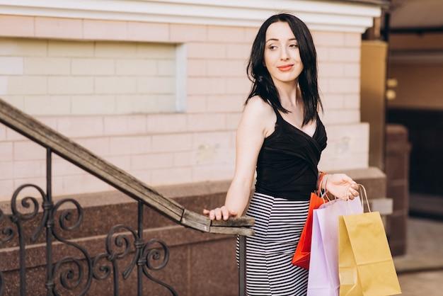 Modisch gekleidete frau mit farbigen einkaufstüten auf der treppe, shopping-konzept