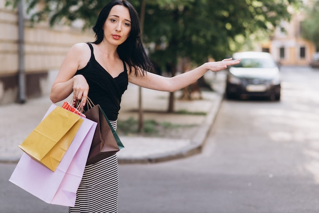Modisch gekleidete frau mit farbigen einkaufstüten fangen ein taxi auf der straße, shopping-konzept